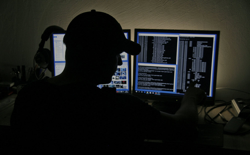 Hacker looking at computer in the dark.