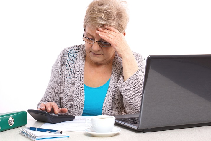 Worried senior woman, an elderly pensioner counting utility bills at her home, concept of financial security in old age